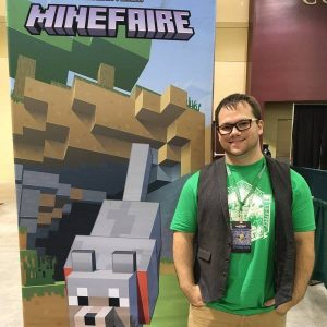 Man sanding in front of a Minecraft Banner with a wolf on it